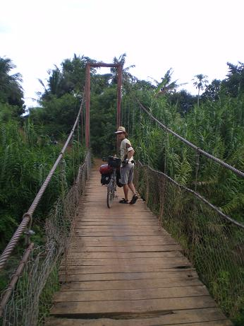 Lionel Margueron standing on the bridge of Cambodian village